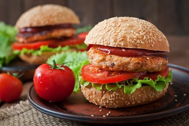 Бутерброд с куриным бургером, помидорами и листьями салата