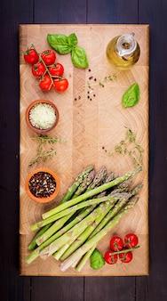 コピースペースを持つ素朴な木製のテーブルに新鮮なグリーンアスパラガス。上面図