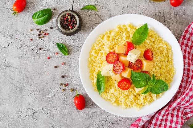 Пшенная каша с сыром, маслом и базиликом в белой миске. вкусная еда. завтрак. вид сверху. плоская планировка