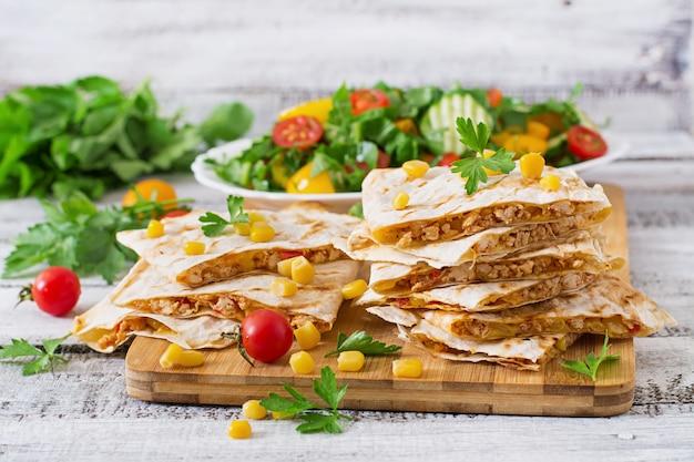 チキン、トウモロコシ、ピーマン、フレッシュサラダのメキシコケサディーヤラップ。