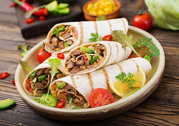 ブリトーは、木製のテーブルで牛肉と野菜をラップします。牛のブリトー、メキシコ料理。メキシコ料理。