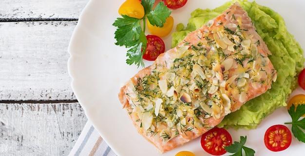 Запеченный лосось с сыром и миндальной корочкой, украшенный картофельным пюре и зеленым горошком