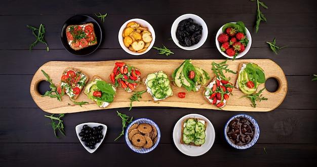 フラット横たわっていた健康的なベジタリアンディナーテーブルの設定。トマト、キュウリ、アボカド、イチゴ、ハーブ、オリーブのサンドイッチ、スナック。クリーンな食事、ビーガンフード