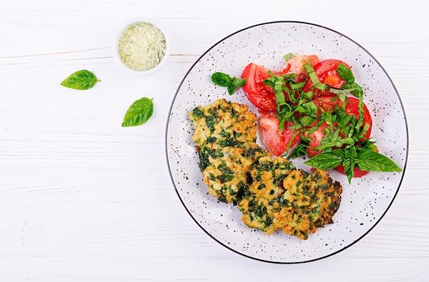 ほうれん草とトマトサラダのおかずと焼きステーキの刻んだ鶏肉の切り身。ヨーロッパ料理。食物。上面図