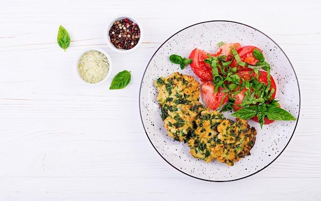 Запеченный стейк нарезанного куриного филе со шпинатом и гарниром из салата из помидоров. европейская кухня диетическое питание вид сверху