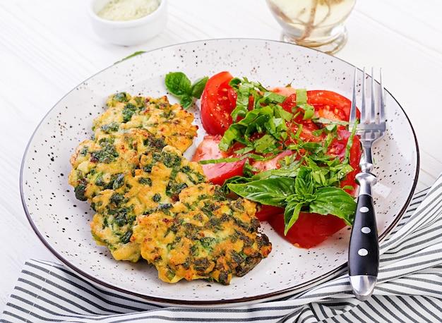 ほうれん草とトマトサラダのおかずと焼きステーキの刻んだ鶏肉の切り身。ヨーロッパ料理。食物。