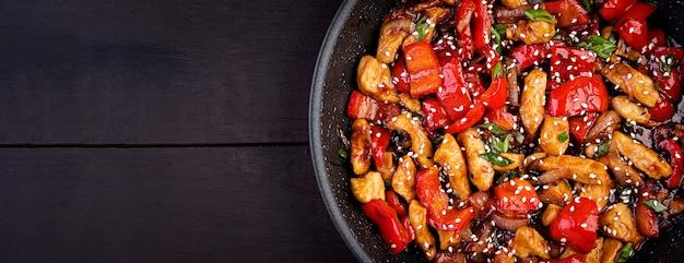 Обжарить курицу, сладкий перец и зеленый лук. вид сверху. азиатская кухня