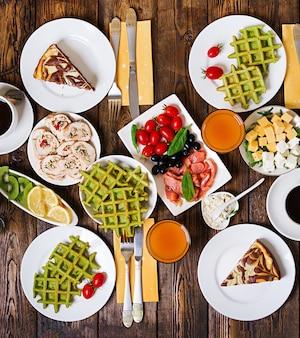 朝食用食品テーブル。お祝いブランチセット、ほうれん草ワッフル、サーモン、チーズ、オリーブ、チキンロール、チーズケーキなどのバラエティーに富んだ食事。上面図。フラットレイ