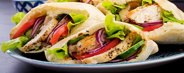 Пита, фаршированная курицей, помидорами и листьями салата на деревянный стол. ближневосточная кухня.