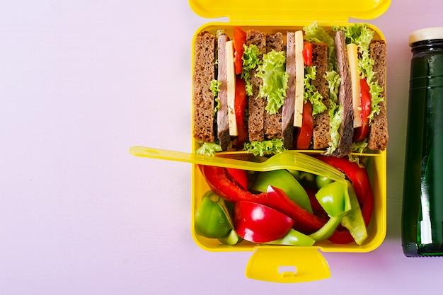 ビーフサンドイッチと新鮮な野菜、ピンクのテーブルに水のボトルと健康的な学校のランチボックス。上面図。フラットレイ