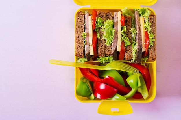 ビーフサンドイッチとピンクのテーブルでの新鮮野菜の健康的な学校ランチボックス。上面図。フラットレイ