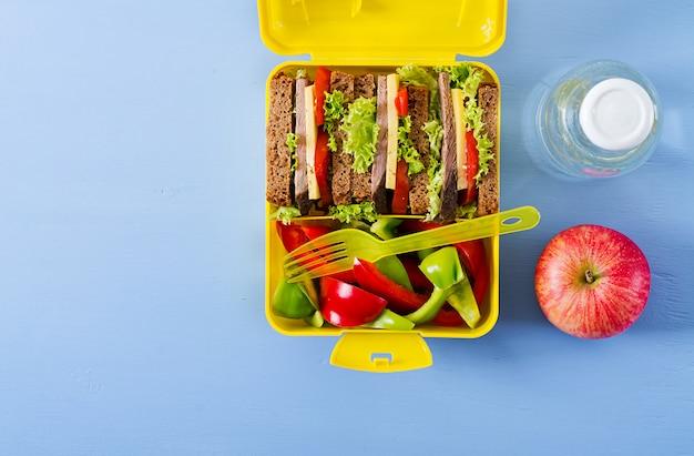 Здоровая коробка школьного обеда с сандвичем говядины и свежими овощами, бутылкой воды и плодоовощами на голубой таблице. вид сверху. плоская планировка