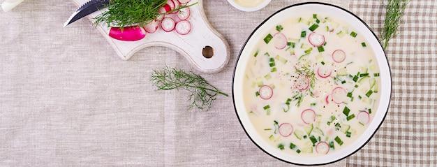 ボウルにヨーグルトと新鮮なキュウリ、大根、ジャガイモ、ソーセージの冷たいスープ。伝統的なロシア料理-オクロシカ。夏の冷製スープ。上面図。