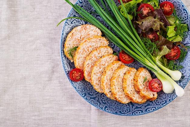 Рулет из куриного мяса с луком и морковью. здоровый рулет. вид сверху
