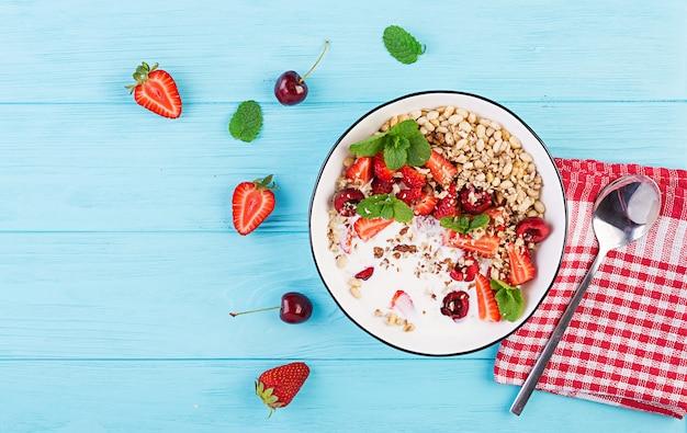 健康的な朝食-木製のテーブルの上にボウルにグラノーラ、イチゴ、チェリー、ナッツ、ヨーグルト。ベジタリアンのコンセプト料理。上面図