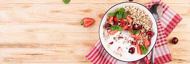 Здоровый завтрак - мюсли, клубника, вишня, орехи и йогурт в миску на деревянном столе. вегетарианская концепция еды. вид сверху