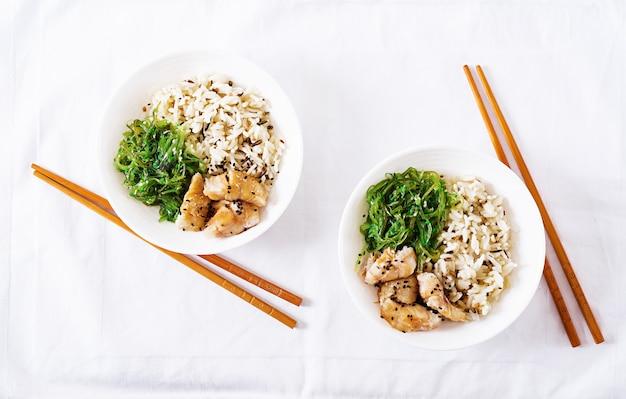 Японская еда. чаша из риса, отварной белой рыбы и вакаме чука или салат из морских водорослей. вид сверху. плоская планировка