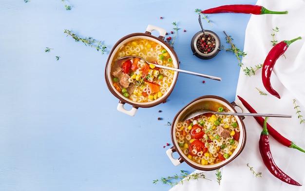 青いパスタのボウルに小さなパスタ、野菜、肉のスープ。イタリア料理。上面図。フラットレイ