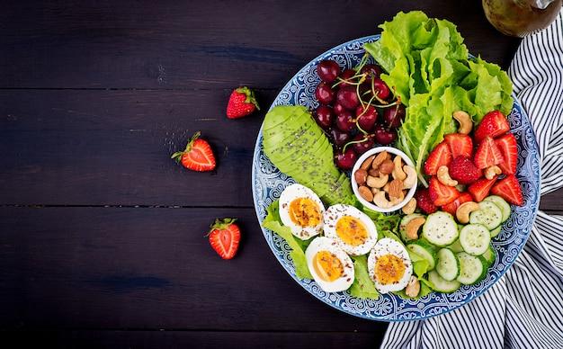Тарелка с палео диетическим питанием. вареные яйца, авокадо, огурец, орехи, вишня и клубника. палео завтрак. вид сверху