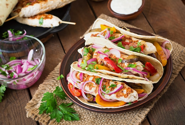 チキン、グリル野菜、赤玉ねぎとメキシコのタコス。