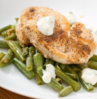 鶏の胸肉のグリル、インゲン、白い皿にソース。