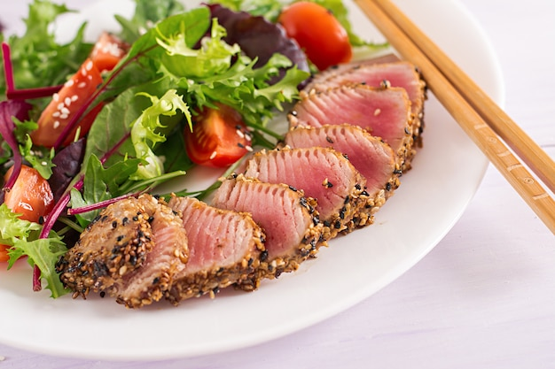 ミディアムレアのアヒマグロとゴマのプレートに新鮮な野菜サラダを添えた日本の伝統的なサラダ。