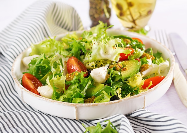 Свежий салат с авокадо, помидорами, оливками и моцареллой в миске. фитнес-питание. вегетарианская еда.