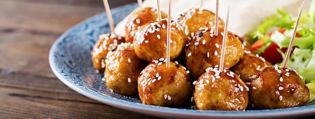 木製のテーブルにモロッコスタイルのピタパンと野菜のプレートに釉薬の甘酸っぱいミートボール。