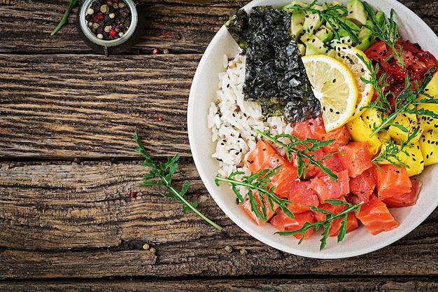 Тушеная рыба из гавайского лосося с рисом, авокадо, манго, помидорами, кунжутом и морскими водорослями.