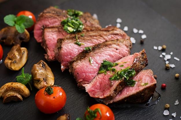 Сочный стейк средней редкости из говядины со специями и овощами гриль.