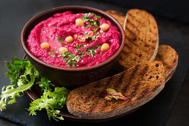 Жареный свекольный хумус с тостами в керамической миске на темном столе