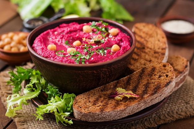 Жареная свекла хумус с тостами в керамической миске на деревянном столе.