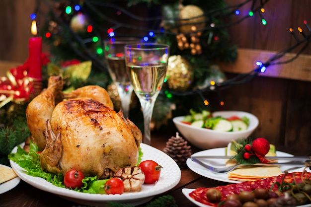 Рождественский стол подается с индейкой, украшен яркой мишурой и свечами