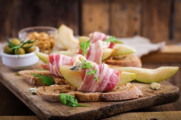 Закуска с грушей, ветчиной, ветчиной, голубым сыром для праздников и тост на деревянный стол.