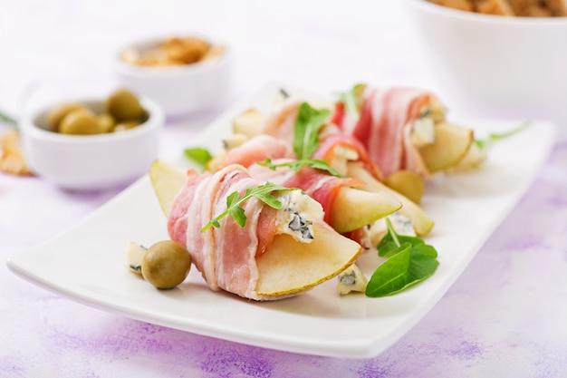 Закуска с грушей, голубым сыром, ветчиной прошутто и тостами для праздников на белой тарелке.