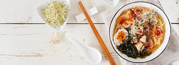 キャベツのキムチ、海藻、卵、キノコ、チーズ豆腐と白い木製のテーブルの上にボウルに味噌麺