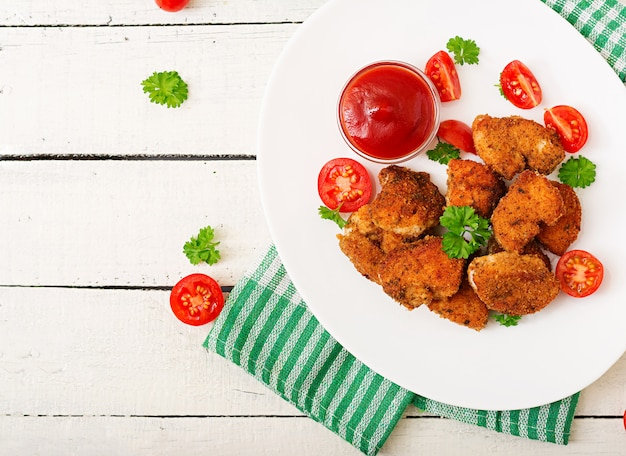 Куриные наггетсы и соус в тарелке на белом деревянном столе