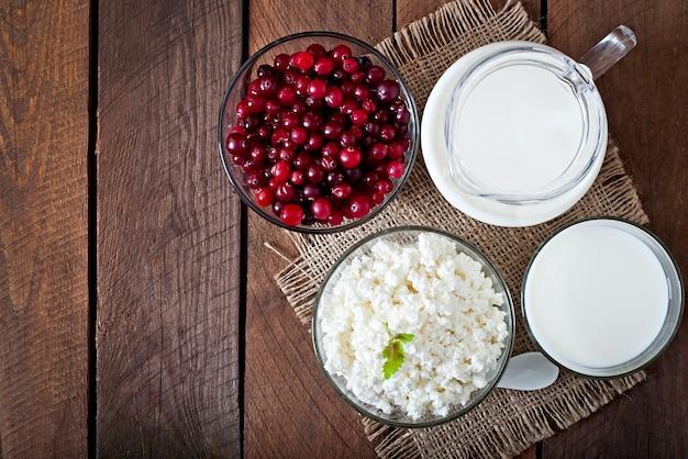 チーズ、ミルク、クランベリー、素朴なスタイルの木製のテーブル