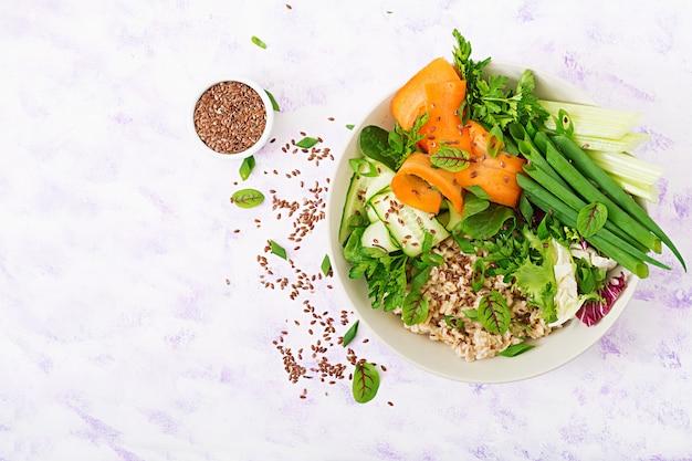 ダイエットメニュー。健康的な生活様式。オート麦のお粥と新鮮な野菜-皿にセロリ、ほうれん草、キュウリ、ニンジン、タマネギ。フラット横たわっていた。上面図