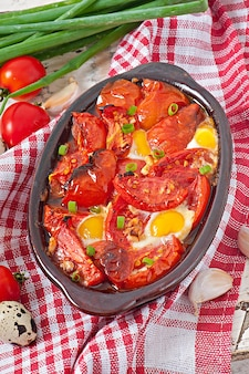Запеченные помидоры с чесноком и яйцом, украшенные зеленым луком