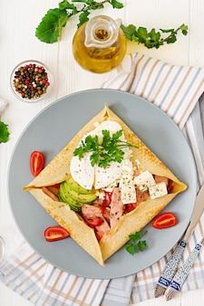Французская кухня. завтрак, обед, закуски. блинчики с яйцом пашот, сыр фета, жареная ветчина, авокадо и помидоры на белом столе. вид сверху