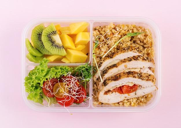 ランチボックスチキン、ブルガー、マイクログリーン、トマト、フルーツ。健康的なフィットネス食品。取り除く。弁当箱。上面図