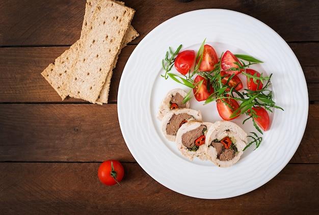 ダイエット焼きチキンは、トマトとルッコラのサラダを詰めた肝臓、唐辛子、ハーブを詰めています。食事メニュー。適切な栄養。上面図