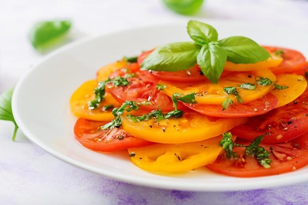 Салат из желтых и красных помидоров с песто из базилика на светлом столе.