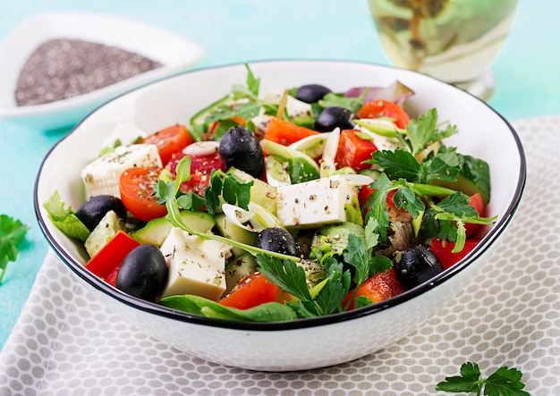 Греческий салат с огурцом, помидорами, сладким перцем, листьями салата, зеленым луком, сыром фета и оливками с оливковым маслом. здоровая пища.
