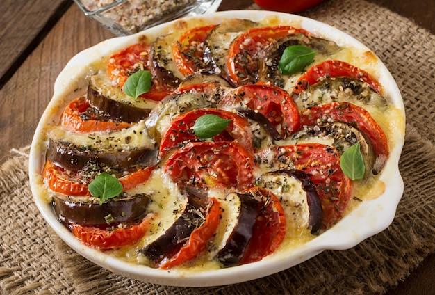 モッツァレラチーズとトマトの準備されたグラタン皿生ナス