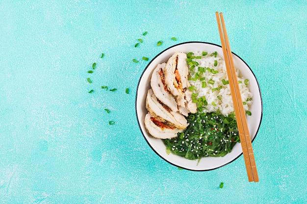 白いボウルのヘルシーサラダ、箸。鶏肉巻き、ご飯、中華、ねぎ。青いテーブル。アジア料理。上面図