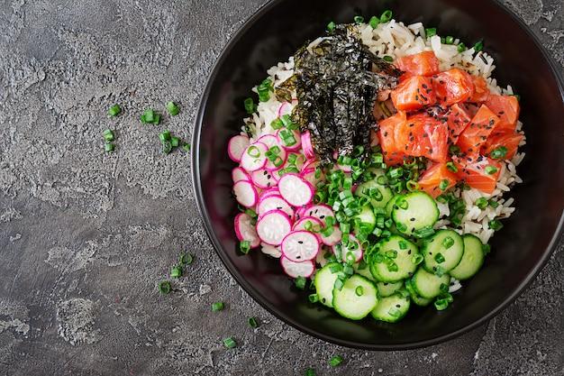 ハワイアンサーモンフィッシュポークボウル、ライス、ラディッシュ、キュウリ、トマト、ゴマ、海藻。仏丼。ダイエット食品。上面図。フラット横たわっていた。