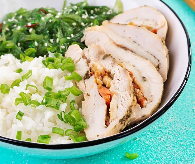白いボウルのヘルシーサラダ、箸。鶏肉巻き、ご飯、中華、ねぎ。青いテーブル。アジア料理。