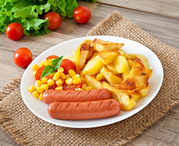Колбаса с жареным картофелем и овощами на тарелке